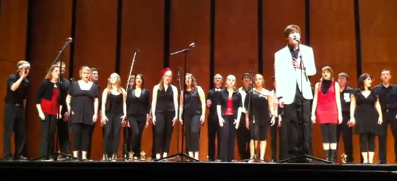 Ben singing on stage at Leon High School with the Mane Event acappella group